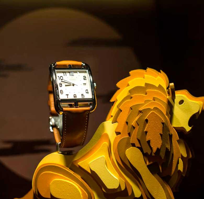 León de madera que expone un reloj para escaparate de Hermes