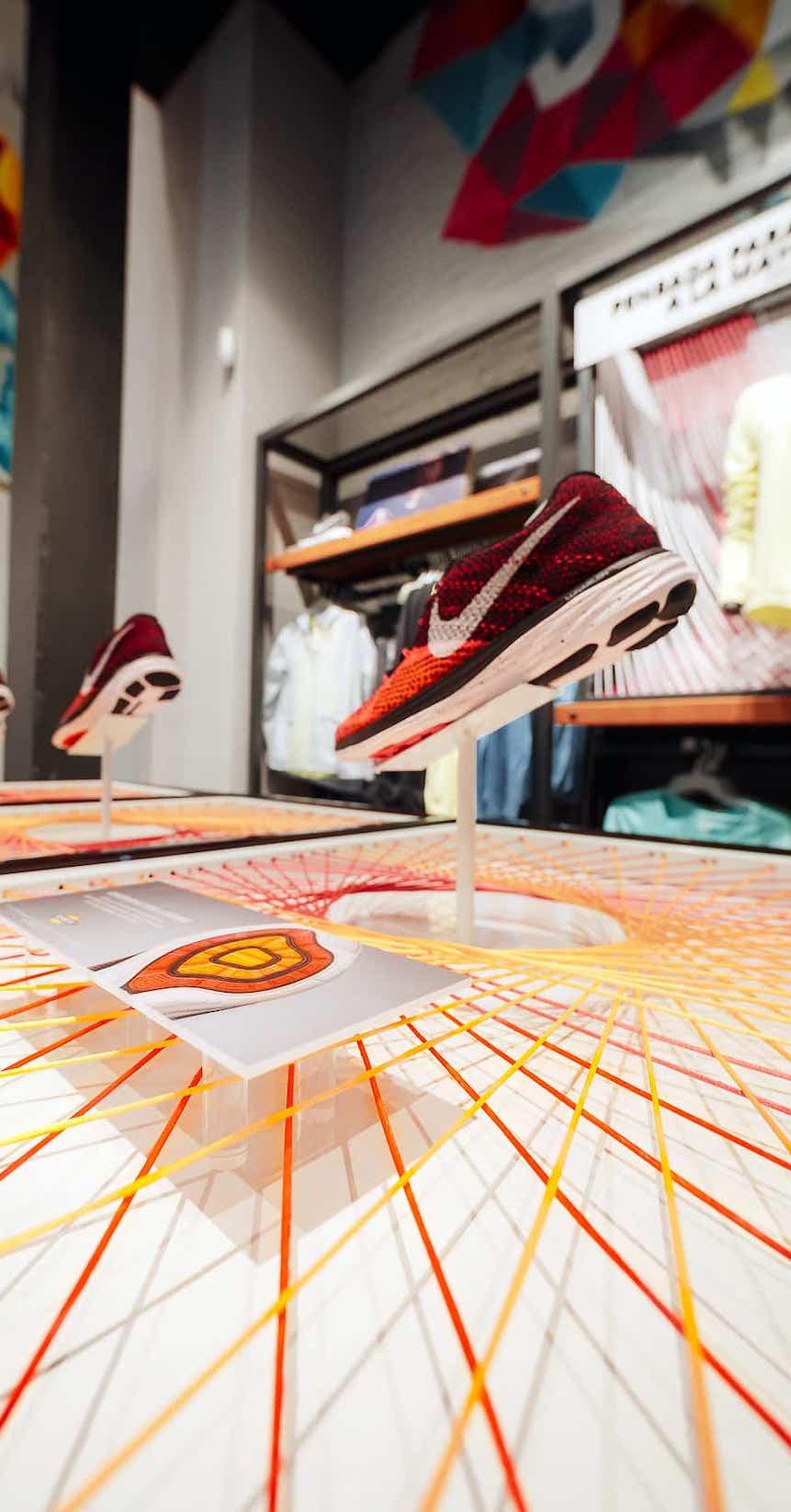 Detalle de mostrador para la colocación de zapatillas montado sobre hilos de diferentes colores en la tienda de Nike de Madrid