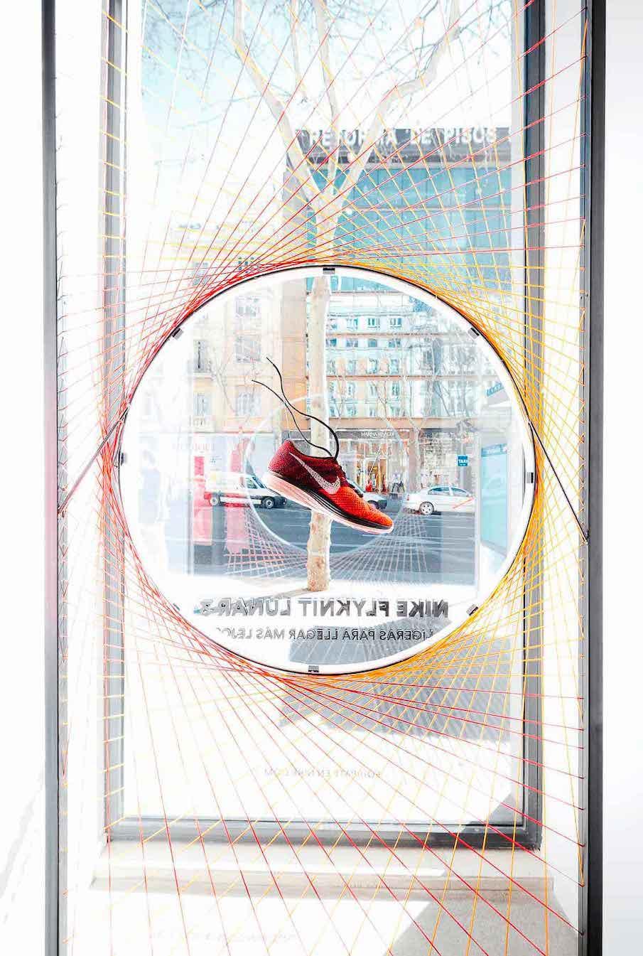 Escaparate con circulo metálico atado con hilos y con neón en tienda de Nike