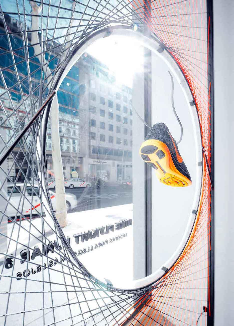 Escaparate con estructura metalica con hilos y neón tienda Nike en Madrid